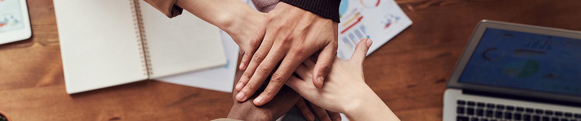 Hände liegen aufeinander und symbolisieren die Partnerschaft